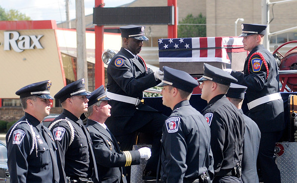 """A symbolic flag draped casket is carried off of AFD's """"Ole Babe."""""""