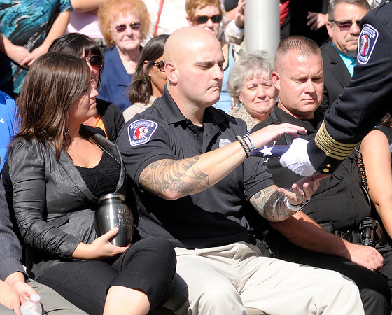 Officer Marty Dulworth accepts a folded flag from Police Chief Larry Crenshaw during a last roll call memorial service on Saturday.