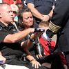 Officer Matt Jarrett accepts a folded flag from Police Chief Larry Crenshaw during a last roll call memorial service on Saturday.