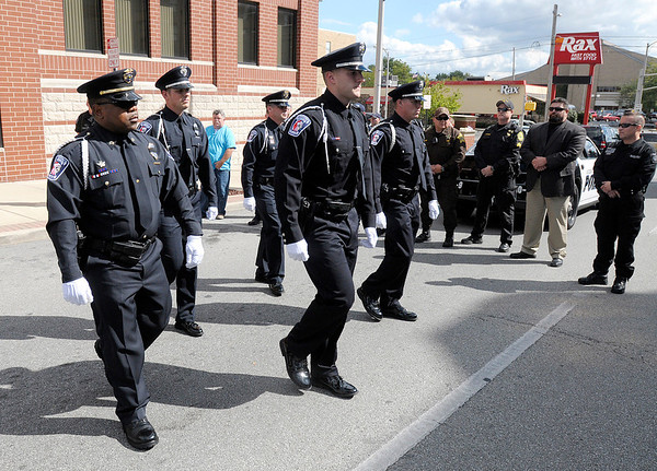 Officers march in formation towards symbolic flag draped caskets.