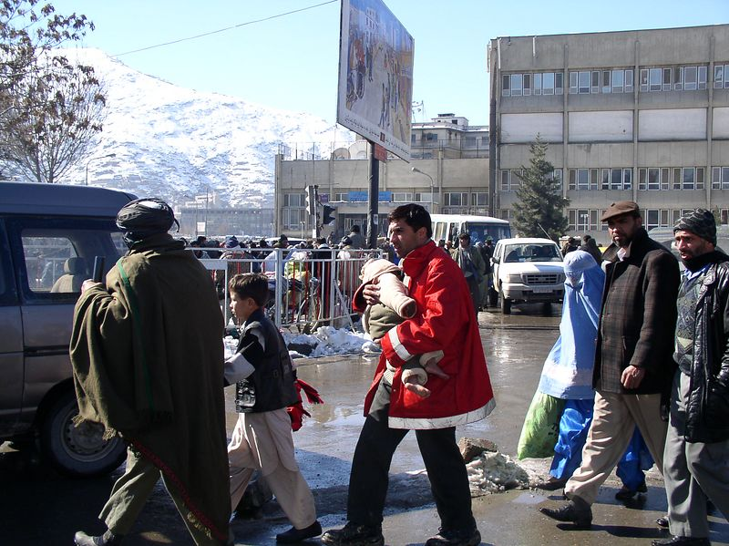 It is cold in Kabul. Notice the baby being carried has no shoes.
