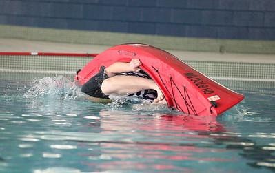 "24FEB13__ Peter Malik of Elyria executes a manuever called a ""wet exit"" as part of the kayak training at Oberlin's Splash Zone. photo by Ray Riedel"