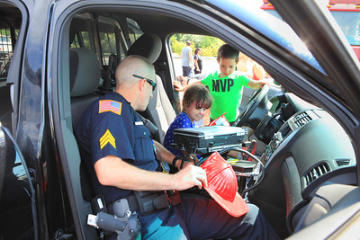 ingston Police Officer Timmy Ballinger shows Abby Renaud and her twin bother Lincoln how to turn on the patrol car lights and siren. Wicked Local Photo/Denise Maccaferri