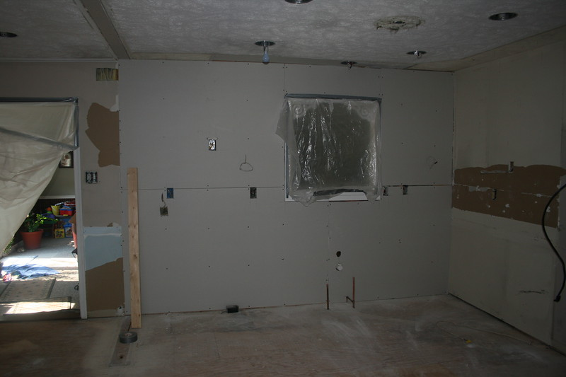dry wall installed on the back wall where sink/frig will go