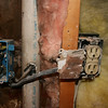 "also discovered when ""brick"" on kitchen wall was removed; check out the plaster over wire; no cover plates and wires going up into a pcv pipe... ok so I know nothing about wiring electric but this can't be right!!! you think?"