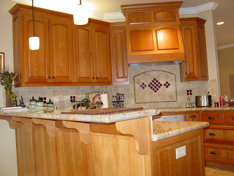 Cherry cabinets with Juliano raised panel door and wood hood surround over cooktop