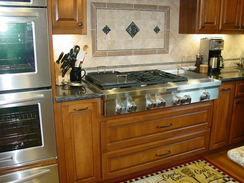 "Alder cabinets with raised panel doors and drawers and 48"" range top"