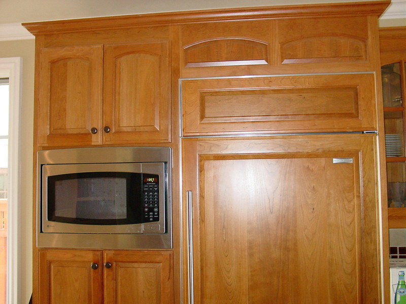 built in Microwave in pantry next to sub zero refer with wood panels on refer door.