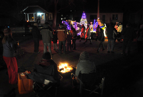Pat Christman<br /> A group gathers around a fire bowl to watch the Kiwanis Holiday Lights parade Friday.