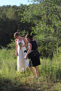 Bride & photographer looking at cactus.