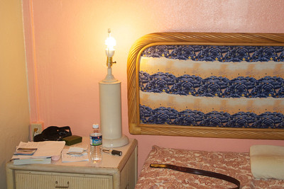 The online photo shows a room with a bed spread. This bed only came with sheets. The online photo shows a lamp with a shade. The lamp in this room has no shade.