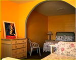 This is the online photo that totally misrepresents the room. The photo has to be very old. The room with yellow walls is now grey and needs paint. It does not look like this photo today. The beds had only sheets on them. They were stained and dirty. No bed spreads. The floors were dirty.