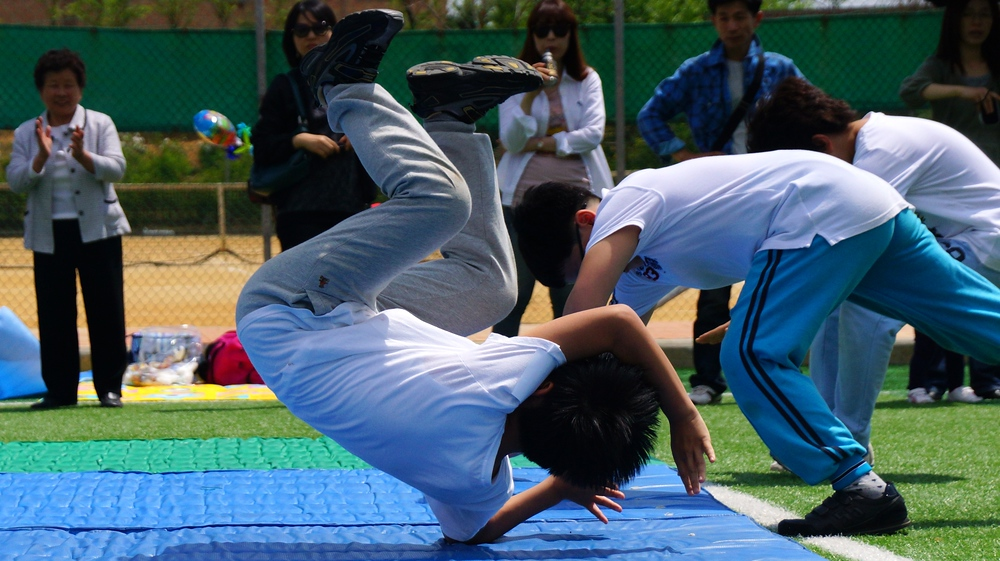 A group of Korean boys take a tumble on the mat doing somersaults.