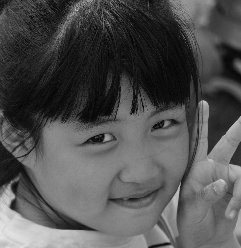 A cute Korean girl poses for the camera with a peace sign.