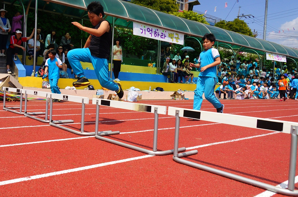 An action shot of some Korean boys leaping over a hurdle.