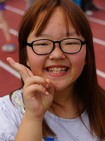 A lovely Korean girl wearing glasses poses for the camera.