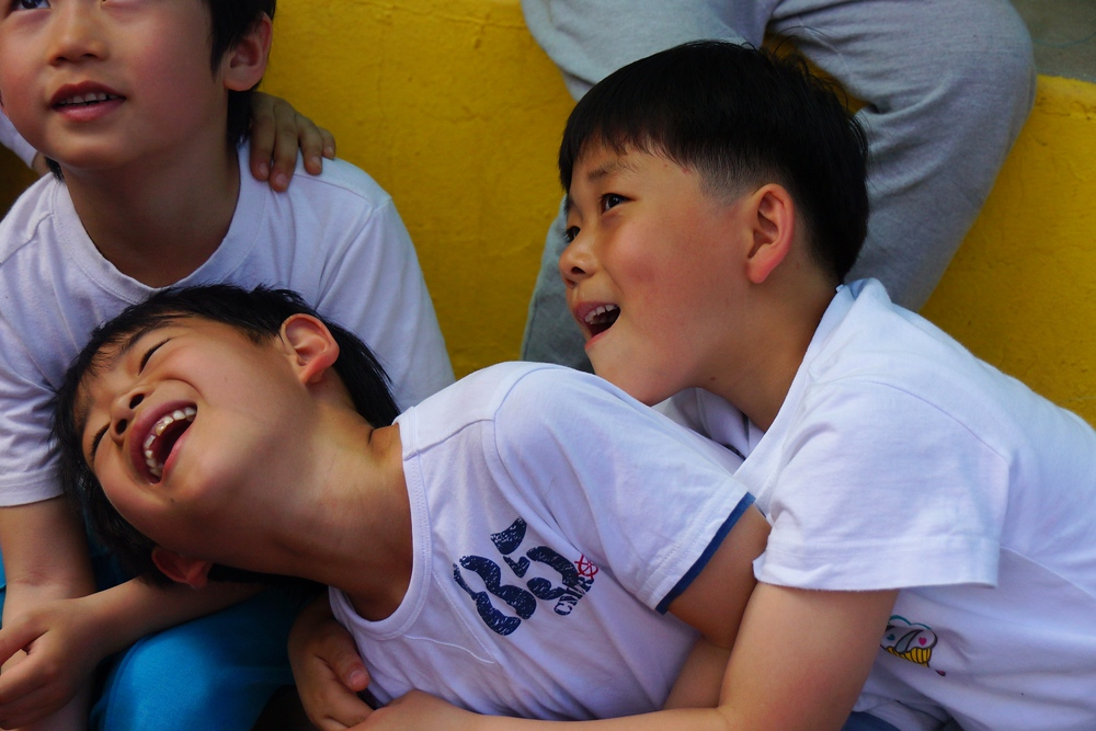 A group of boys laugh and share a candid moment.