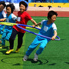 A group of Korean boys race around a pylon with hoops.