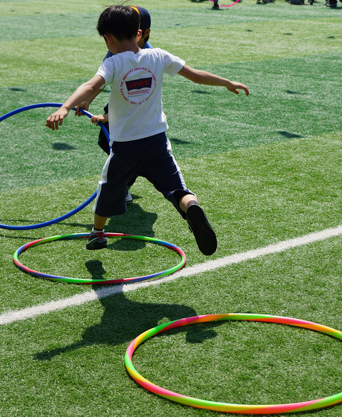 A Korean boy leaps from hoop to hoop.