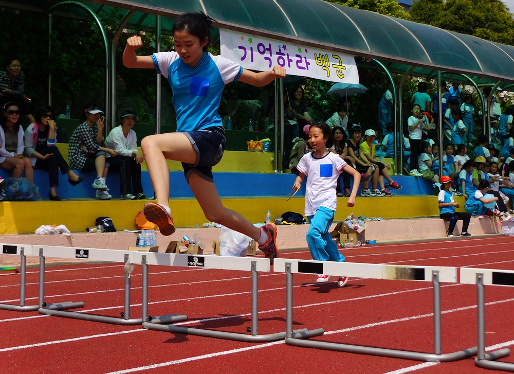 A Korean girl leaps to clear a hurdle on Sports Day.