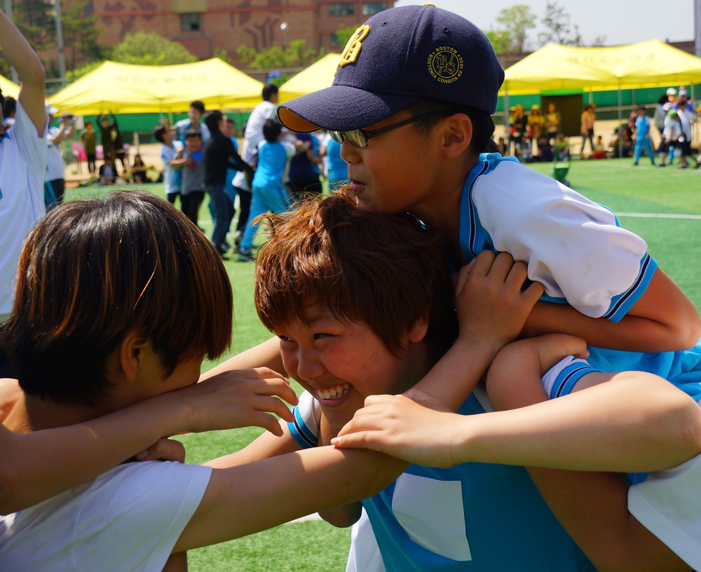 Some Korean boys enjoy piggyback wars with plenty of smiling faces.