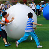 An action shot of some Korean boys competing in a ball rolling competition.