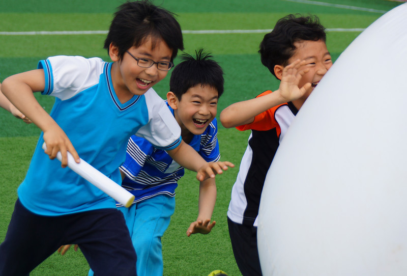 Korean students push a large white ball while thoroughly enjoying the moment.