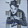 artwork of charlie chaplin as the little tramp from the film Modern Times, painted on a building in Switzerland