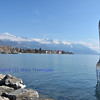 Giant fork planted in Lake Geneva, Switzerland. In the background the bernese alps and the town of Montreux