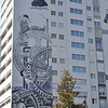 artwork on a block of flats, containing images of charlie chaplin from his hit movie Modern Times.