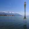 Giant fork sculpture inserted into lake Geneva Switzerland. In the background the town of Montreux and the bernese alps