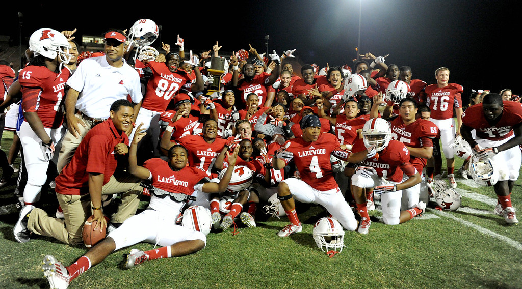 . Lakewood defeated Mayfair 43-0 and poses with the Milk Bucket Trophy at Bellflower High School in Bellflower, CA. on September 13, 2013. (Photo by Sean Hiller/Press Telegram)