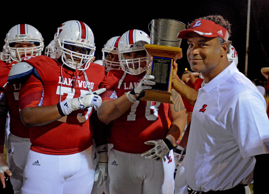 . Lakewood\'s Coach Kenric Jameison holds the Milk Bucket Trophy with Damonte Spillman,left, and Toma Suafoa, center, after defeating Mayfair 43-0 at Bellflower High School in Bellflower, CA. on September 13, 2013. (Photo by Sean Hiller/Press Telegram)