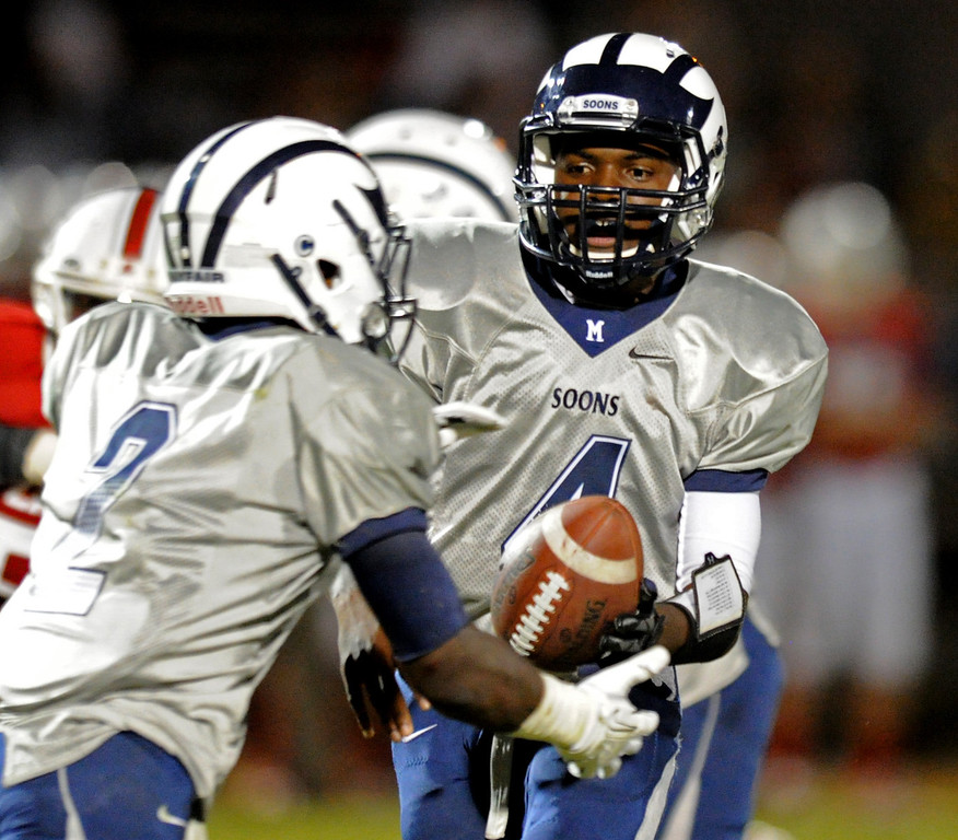 . Mayfair\'s quarterback Isaiah Jackson, right, hands off to Faizon Creighton (2) against Lakewood as they play at Bellflower High School for the Milk Bucket Trophy in Bellflower, CA. on September 13, 2013. (Photo by Sean Hiller/Press Telegram)