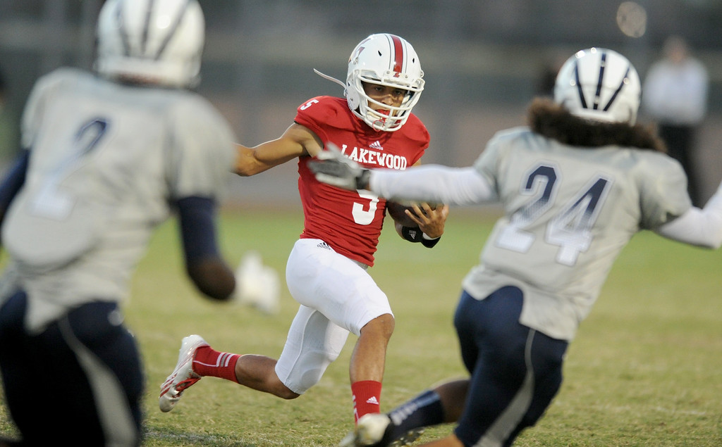 . Lakewood\'s quarterback Kyle Parra on a keeper against Mayfair\'s Faizon Creighton (2),left, and Errol Gonzalez (24), as they play at Bellflower High School for the Milk Bucket Trophy in Bellflower, CA. on September 13, 2013. (Photo by Sean Hiller/Press Telegram)