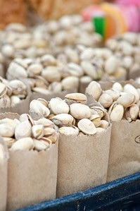 Small paper bags of pistachios sold in a market.