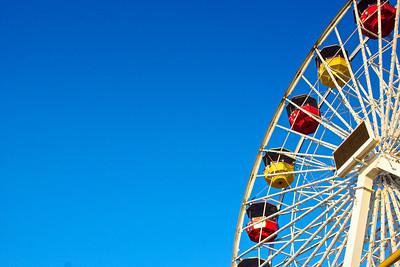 Gondolas ride around the top of a ferris wheel on California's Santa Monica Pier.