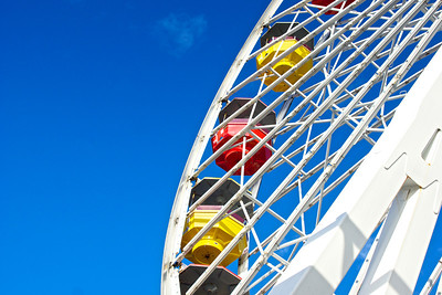 Painted white steel structure of the ferris wheel holding red and yellow gondolas.