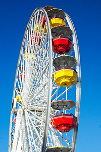 Ferris wheel stands tall against a bright blue sky.