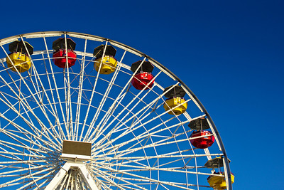 Top quarter of a ferris wheel with red and yellow gondolas hanging from the structure.