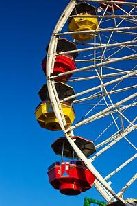 Bright, shining gondolas hang from the Ferris Wheel on California's Santa Monica Pier.