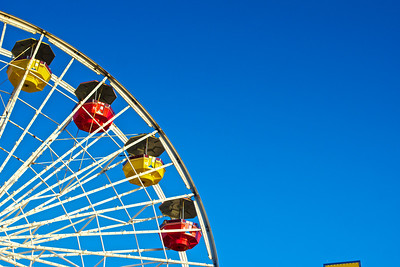 Red and yellow gondolas hang from the Ferris Wheel on California's Santa Monica Pier.