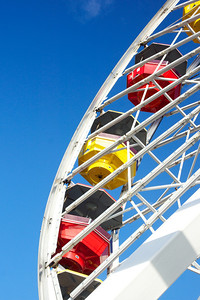 View through the structure of a ferris wheel to the red and yellow gondolas.