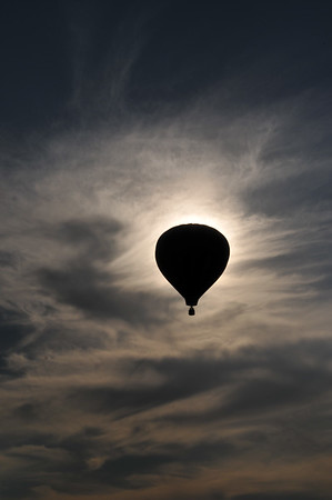Balloon Eclipse #1. Number 1 in a series of 4, a hot air balloon floats in front of the sun, creating a silhouette of the balloon.
