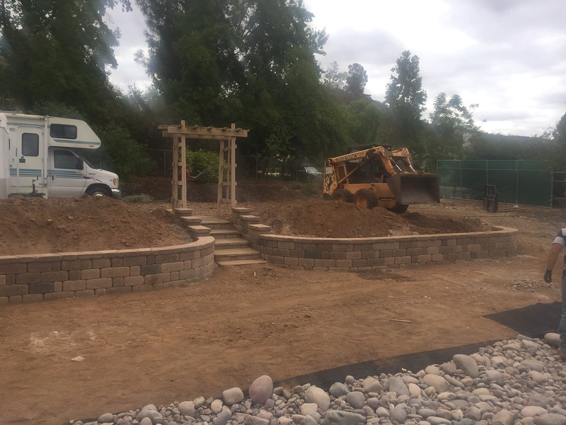 The retaining walls in back are done. The piles of dirt from the old lawn area get pushed back in place. Some of the extra dirt went back by the fruit trees.