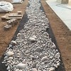 Lots of rocks for the dry creek bed feature. The underlayment will prevent any weeds from growing up through the stones.