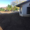 A new concrete path from the front yard to the back patio will go here.