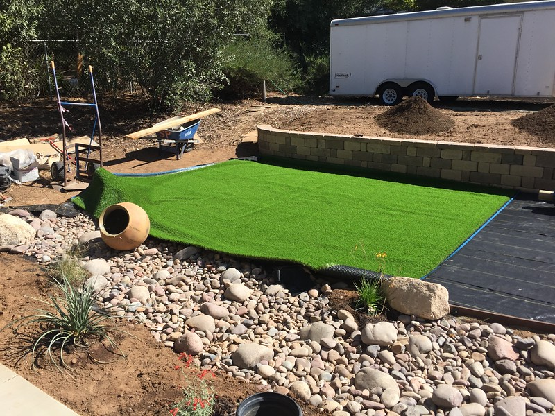 The turf gets laid out and trimmed to the edging.