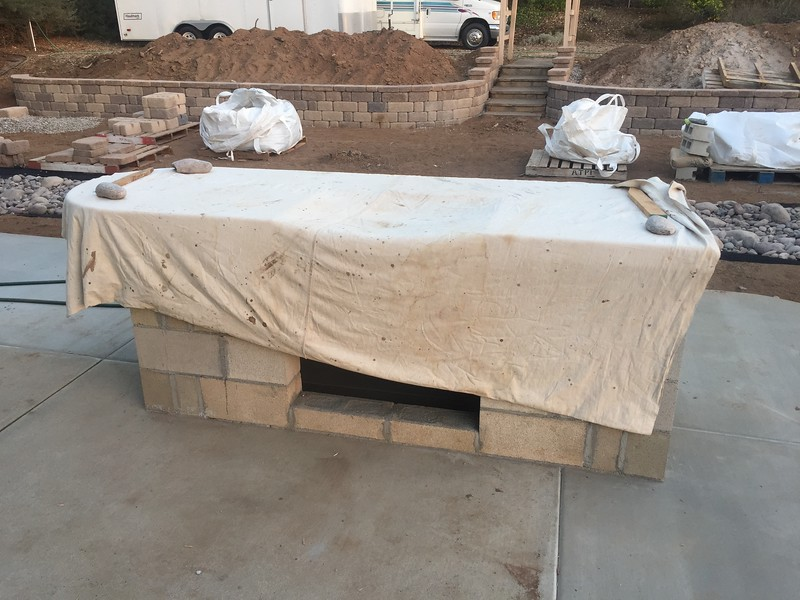 The top of the BBQ island is poured concrete. They built up a wooden form underneath and then poured the top and let it dry up slowly.