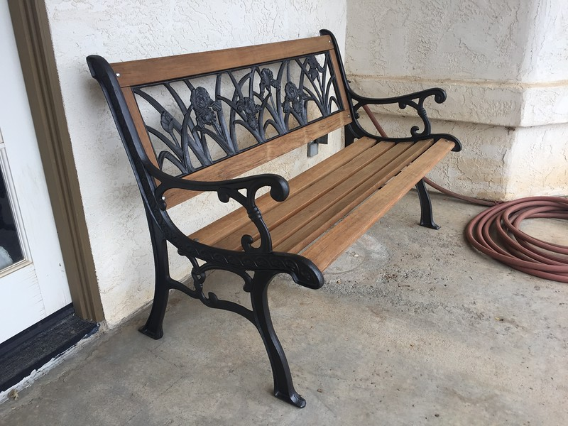 The old bench is restored with new teak boards and a nice oil rubbed bronze paint job on the iron parts.